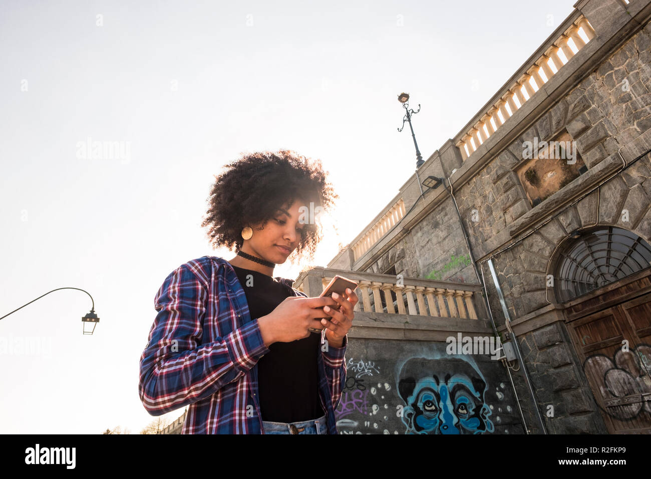 Schöne junge Frau zu Fuß in die Stadt mit einem smart phone Nachrichten an Freunde oder prüfen Sie auf e-Mail und soziale Netzwerke zu senden profilesl Jugendlicher Menschen in städtischen Wettbewerb und Lebensstil Stockbild