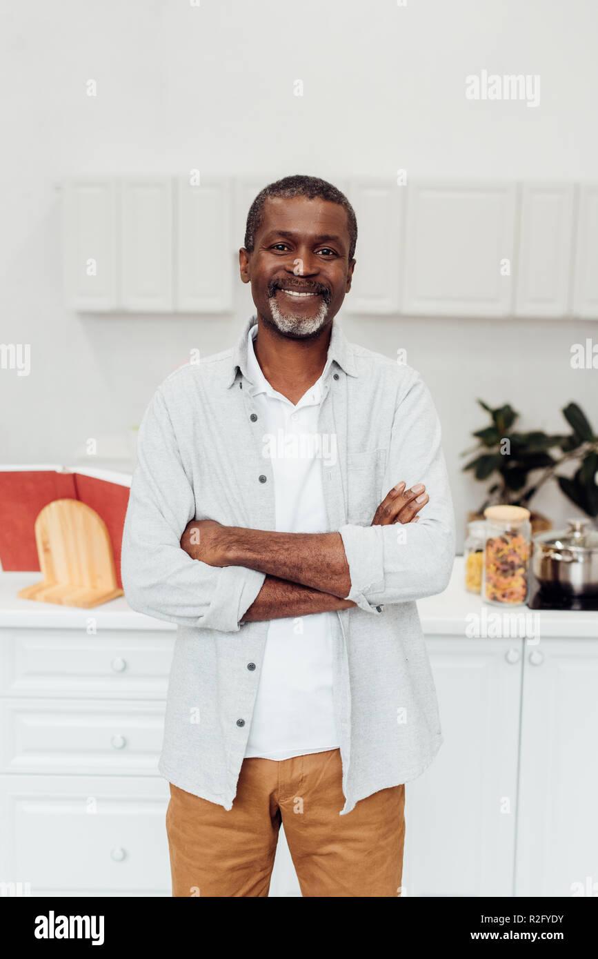 Happy african american reifer Mann mit verschränkten Armen stehend an Küche Stockbild