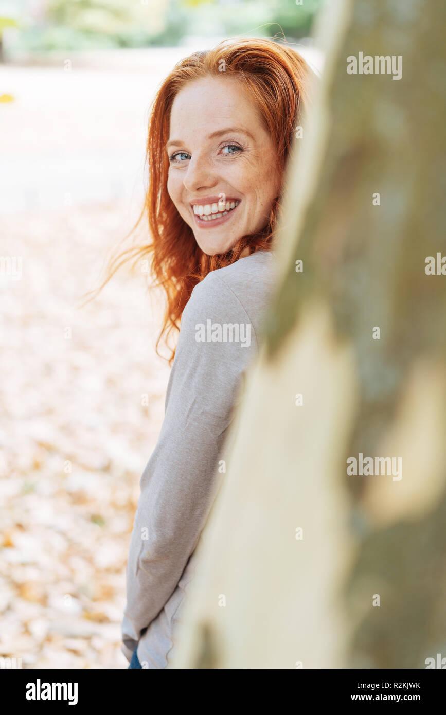 Cute charismatische junge rothaarige Frau gegen einen Baum zurück zu schauen hinter die Amtsleitung an der Kamera mit einem glücklichen Lächeln lehnte Stockfoto