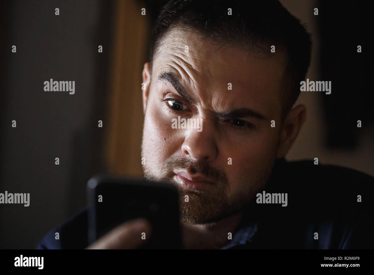 Der bärtige Mann mittleren Alters amazedly Suchen in dem dunklen Raum an das Smartphone. Close Up. Stockfoto