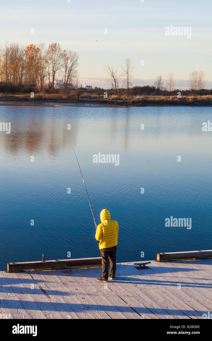 797ea21bc1580c Fischer mit einem Casting Rute auf einer schwimmenden Dock trägt eine gelbe  Jacke, Stockbild
