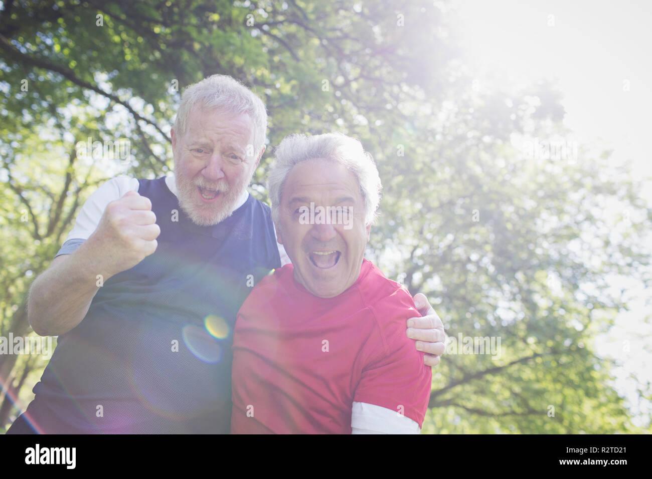 Portrait exuberant Aktive ältere Männer Jubel im sonnigen Park Stockbild