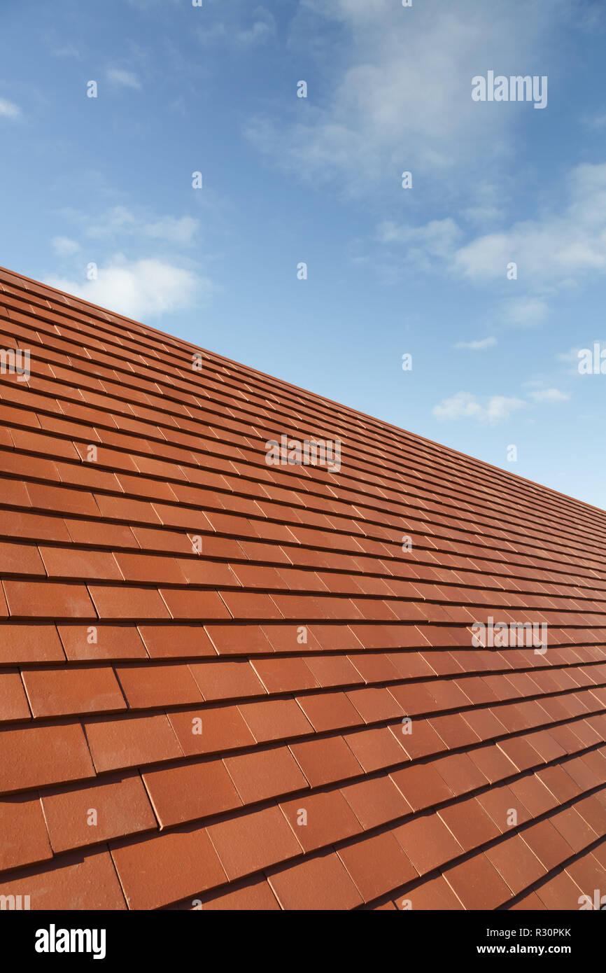 Neue traditionelle Flachziegel auf einem Hausdach gegen einen blauen Himmel mit Kopie Raum Stockfoto