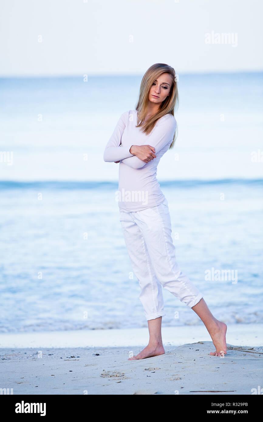 f67f255eaa012 Junge attraktive blonde Frau ist zu Fuß am Strand Stockfoto