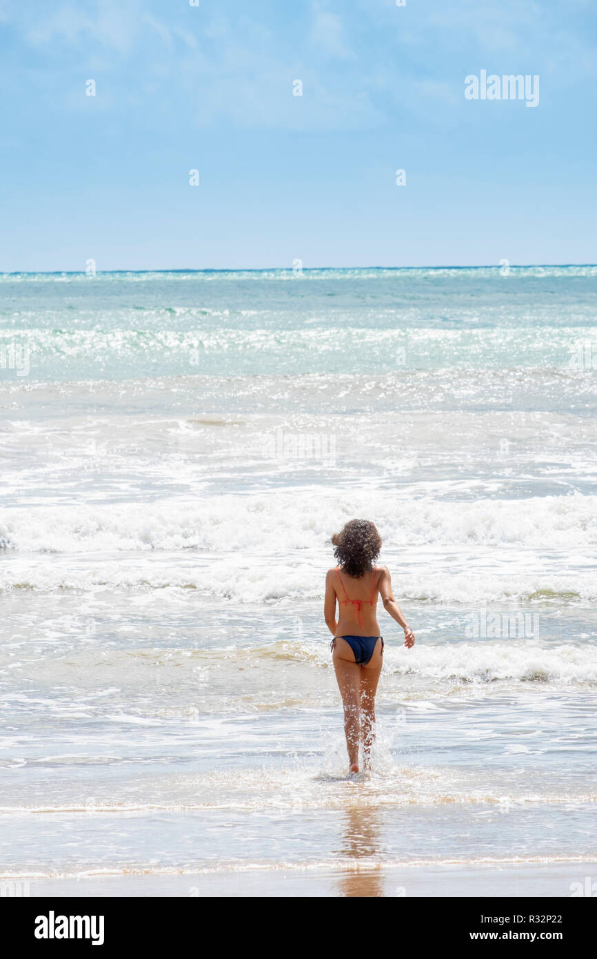 Eine schöne junge Frau auf einem weissen Sandstrand mit Palmen Strand in den Tropen Stockbild