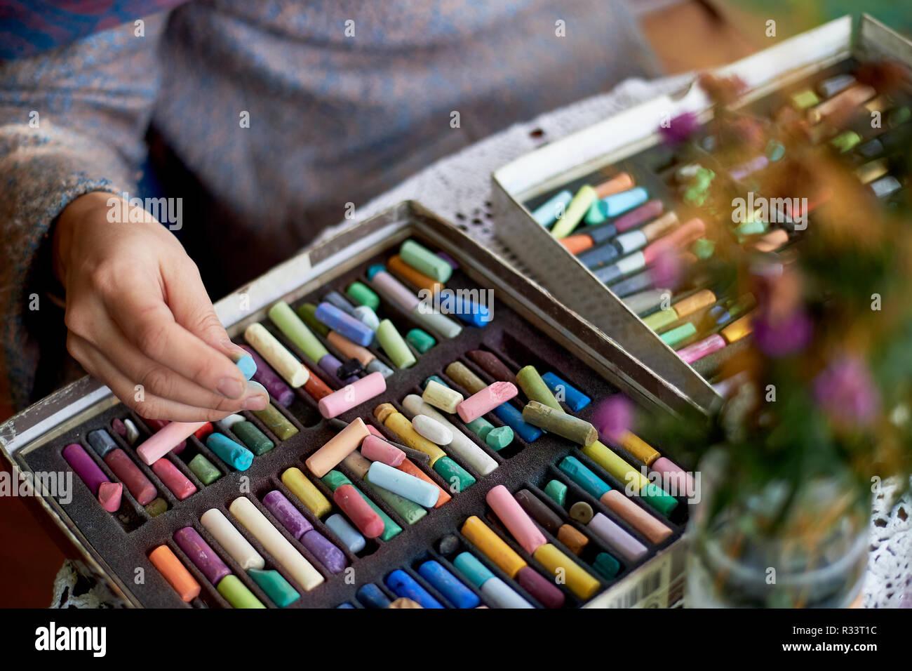 Box mit Pastellkreiden und Artist's Händen. Zeichnung mit trockener pastell Stockbild