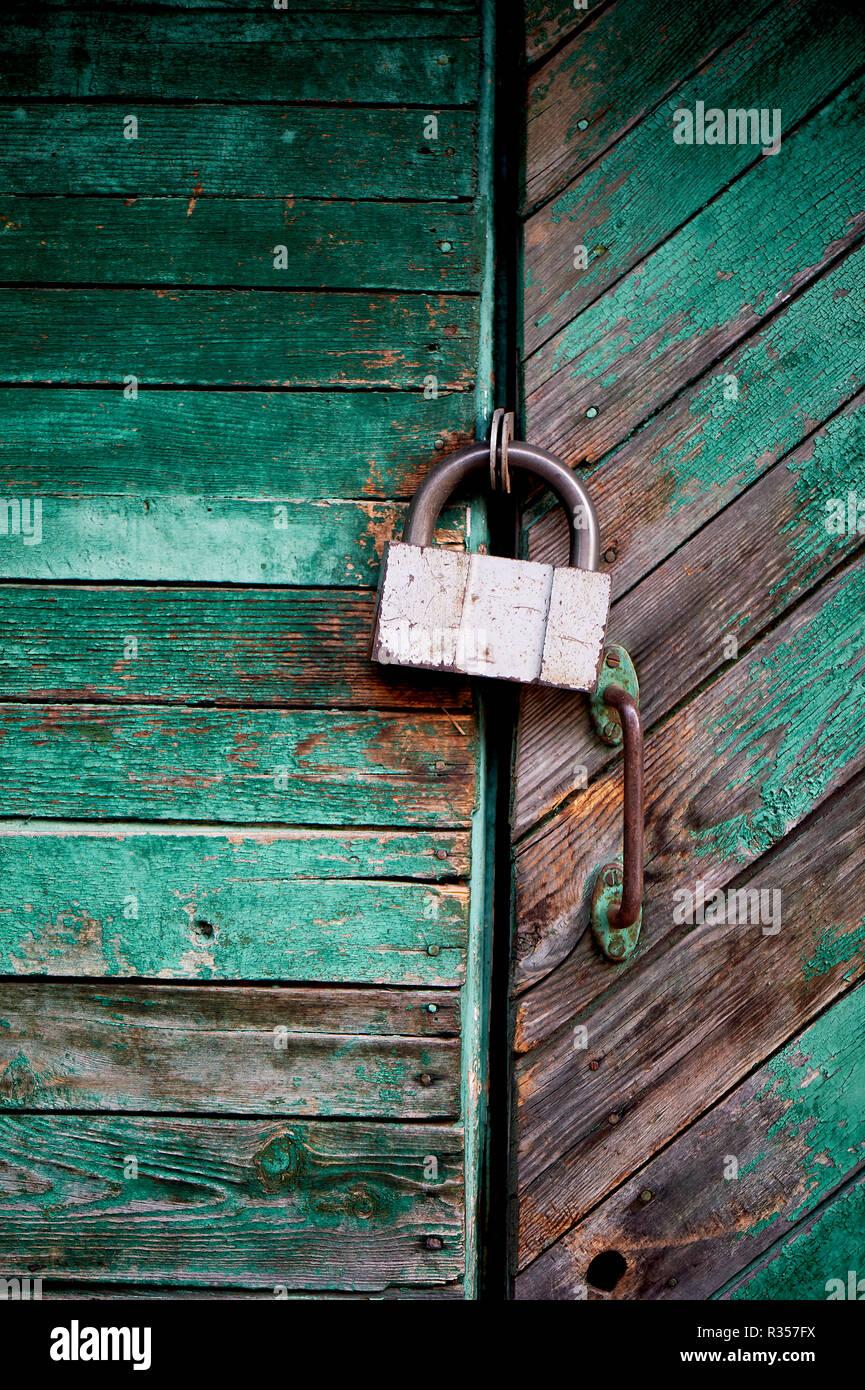 Alten grünen Tür oder Wand eines Holz- Haus im rustikalen Stil, mit abblätternder Farbe. An der Tür hängt ein altes Metall sperren Stockbild