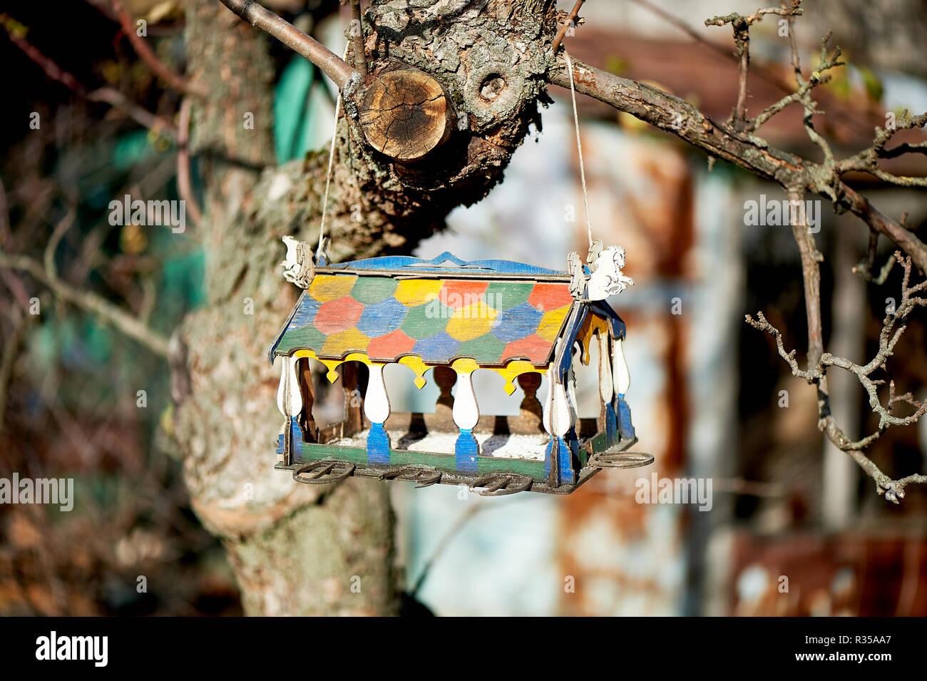 Bemalte hölzerne Haus Vogelhaus auf einen Baum im Garten. Pflege und Fütterung von Vögeln. Stockbild
