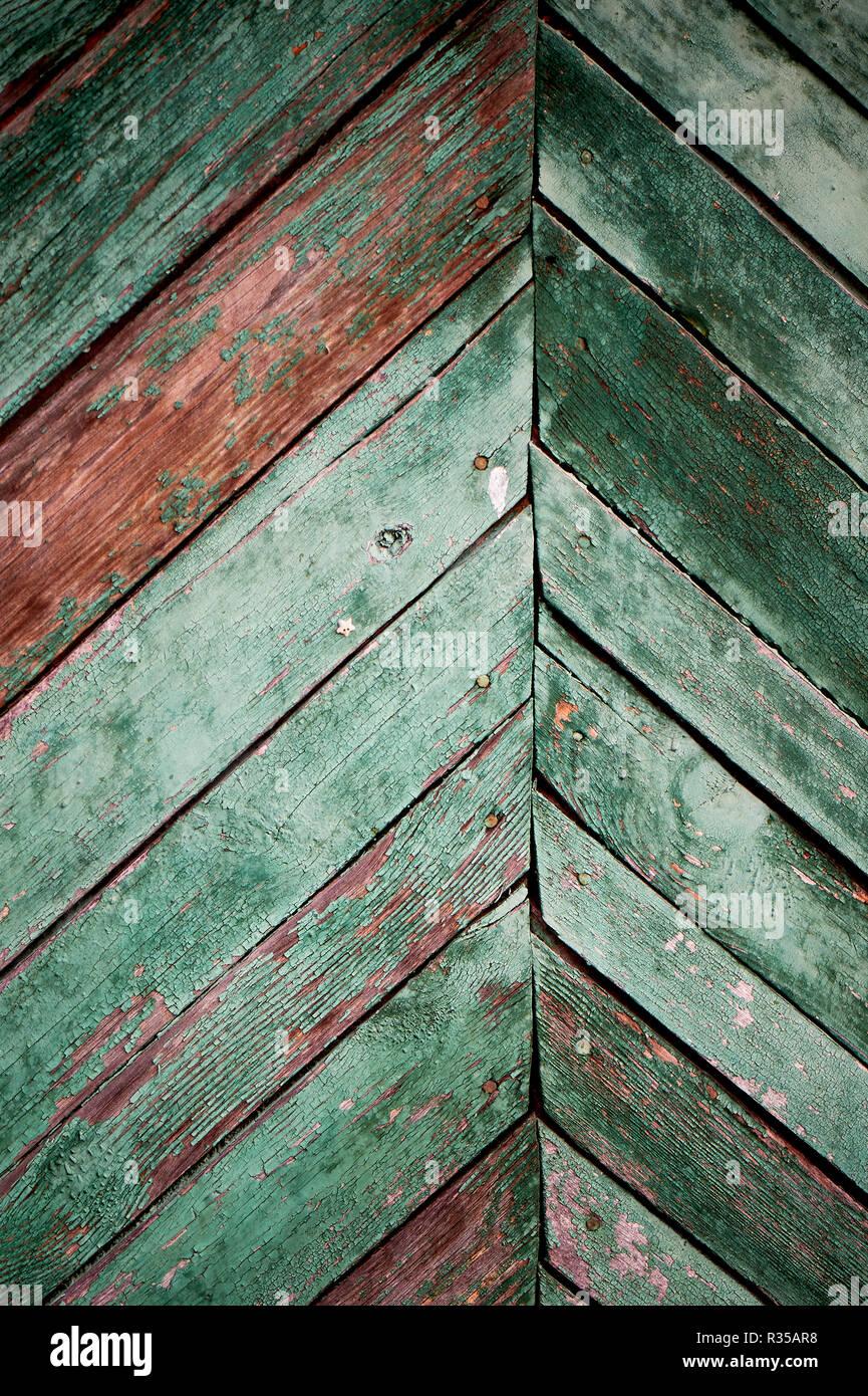 Alten grünen Tür oder Wand eines Holz- Haus im rustikalen Stil, mit abblätternder Farbe. Stockbild