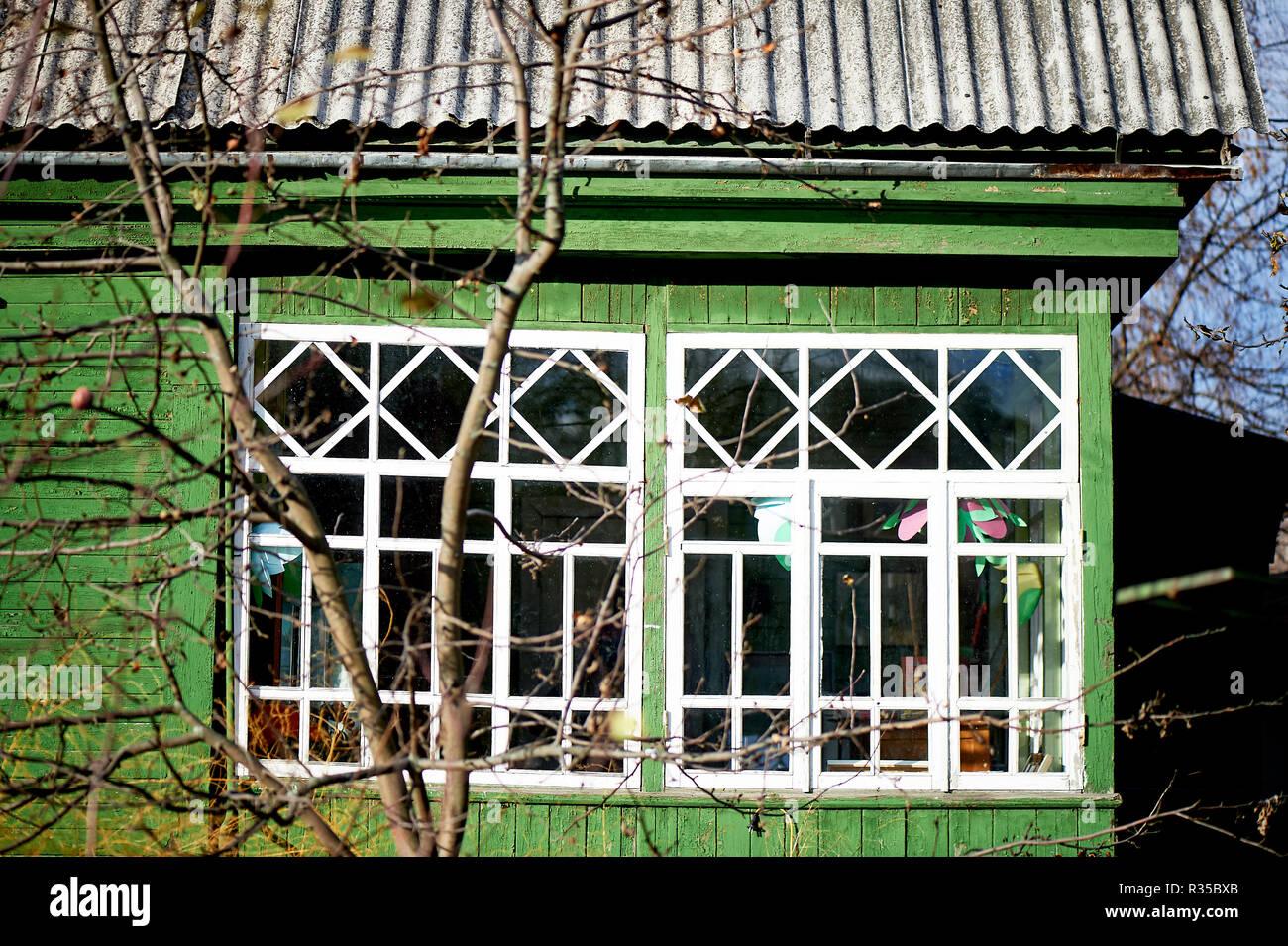 Alten grünen Holz- Haus mit weißen Fenstern. Verglaste Veranda Stockbild