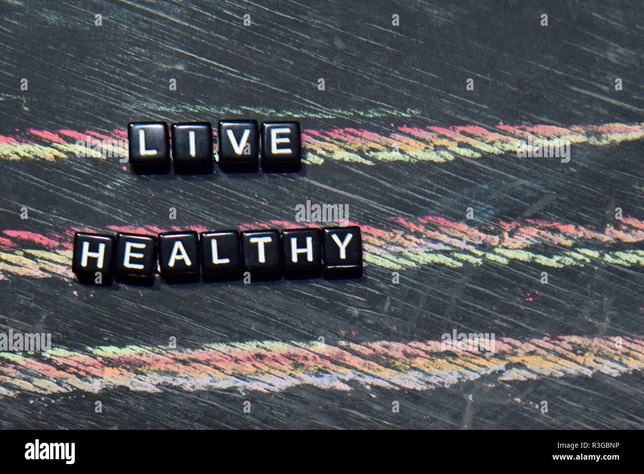 Gesund leben mit Holzblöcken abstützen. Kreuz verarbeitete Bild mit blackboard Hintergrund. Inspiration, Bildung und Motivation Konzepte mit den Worten Gegenstand Stockbild