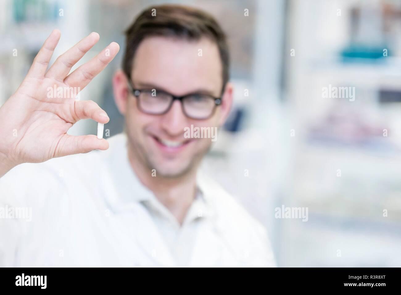 Portrait von lächelnden Apotheker holding Pille. Stockbild