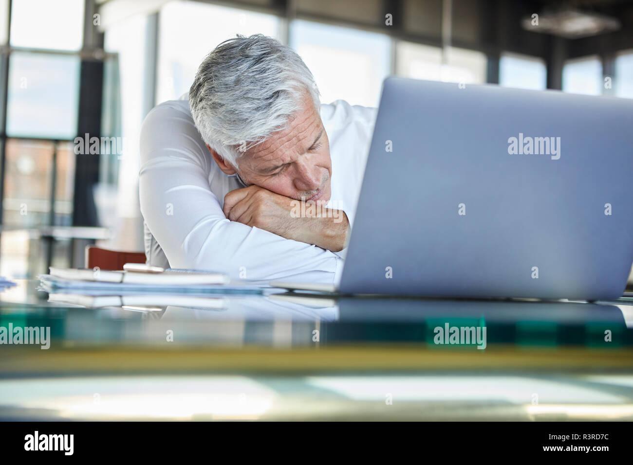 Erschöpft Geschäftsmann schlafen vor Laptop Stockfoto