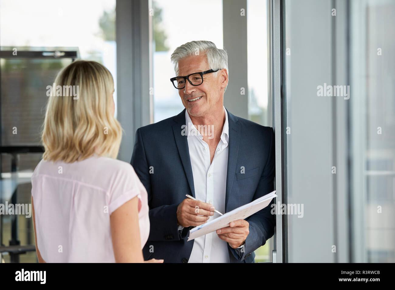 Kaufmann und Frau im Büro, diskutieren, halten Dokumente Stockfoto