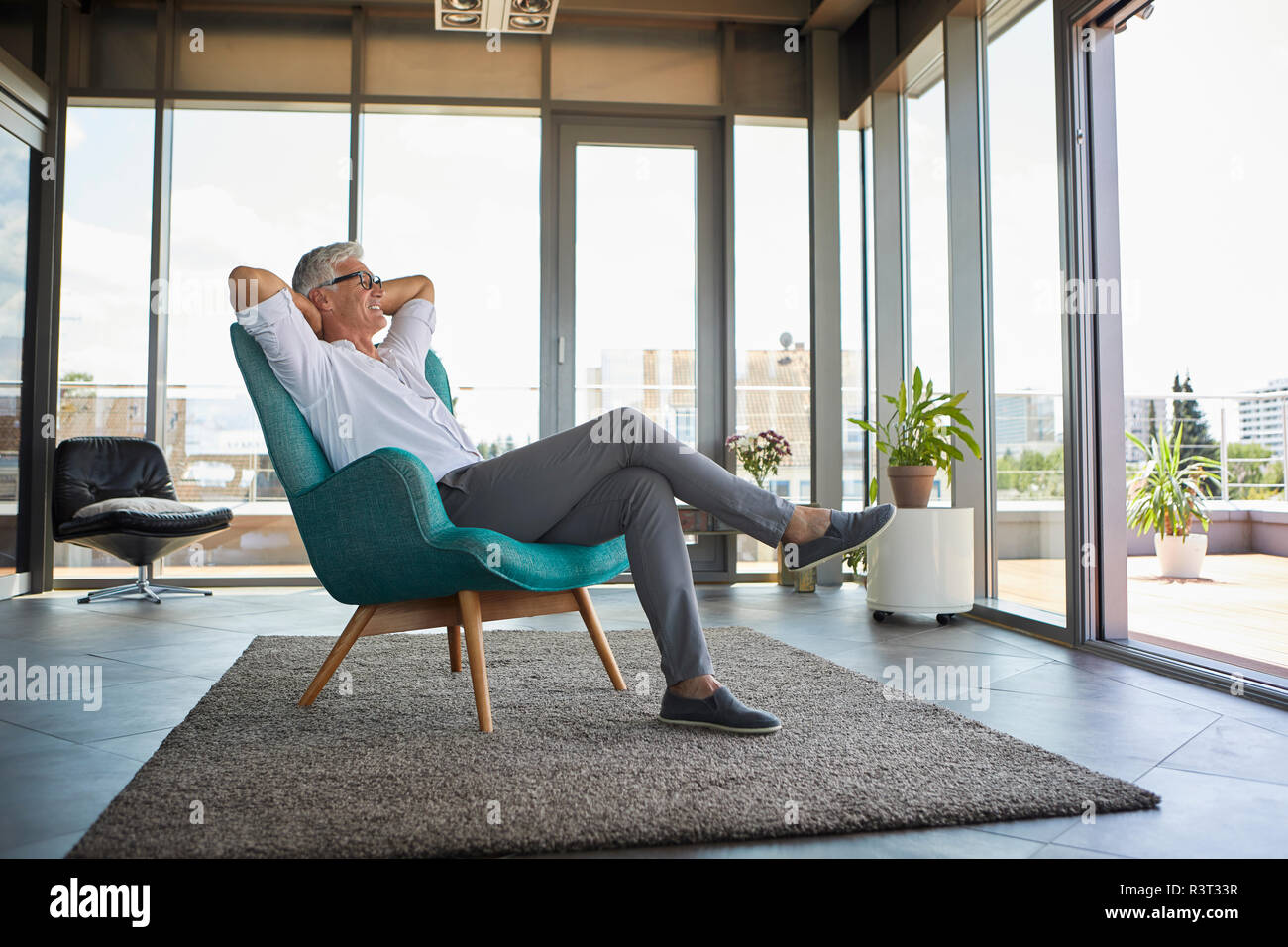 Lächelnd reifer Mann im Sessel am Fenster zu Hause Stockfoto