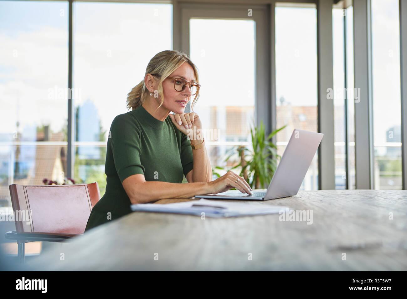 Reife Frau mit Laptop auf dem Tisch zu Hause Stockfoto