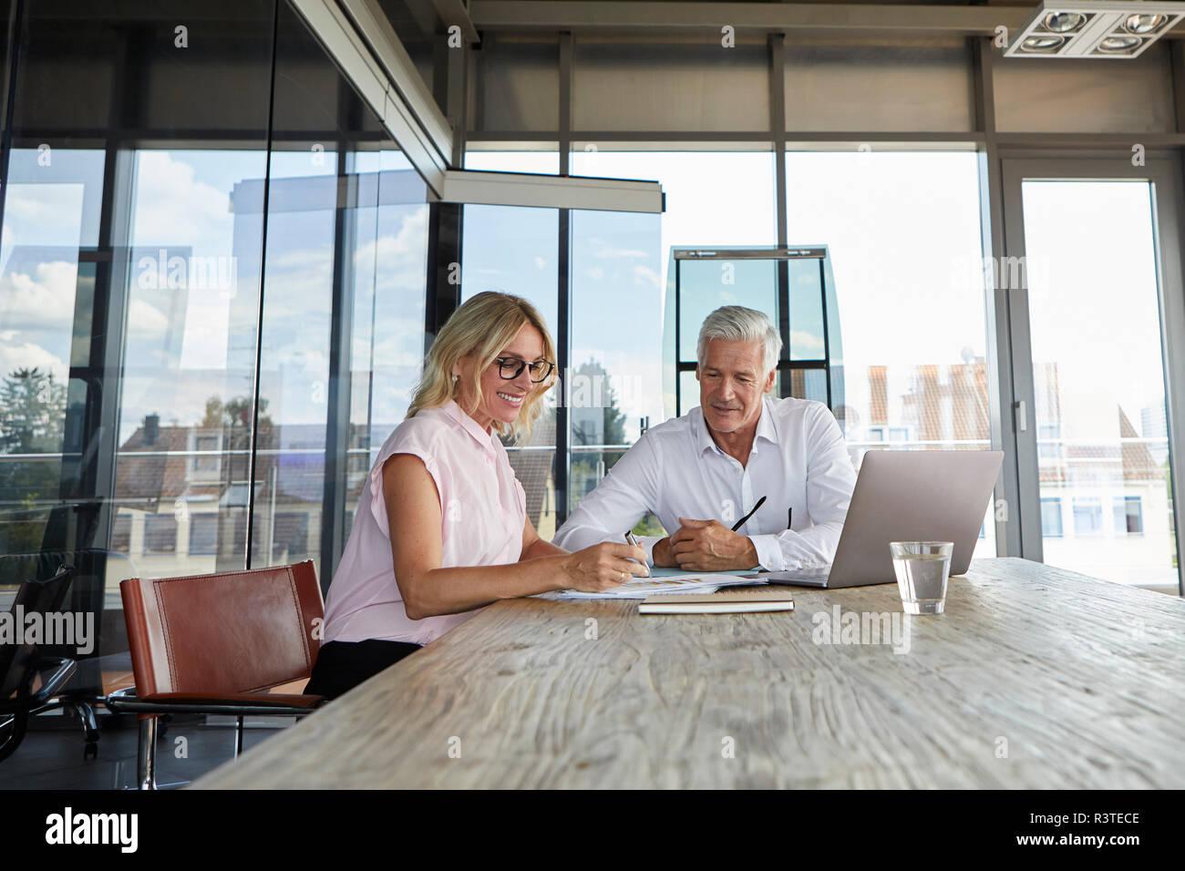 Geschäftsmann snd Frau sitzt im Büro, diskutieren Projekt Stockfoto