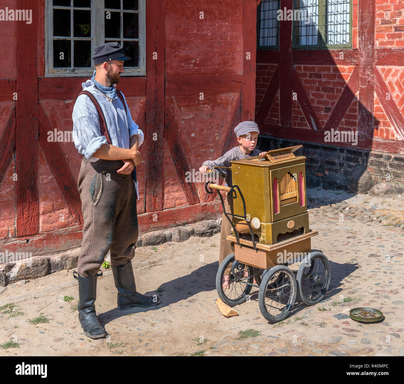 Mann und Junge in historischen Kostümen spielen Drehorgel, Marktplatz (Torvet), der Altstadt (Den Gamle By), ein Freilichtmuseum in Århus, Dänemark Stockbild