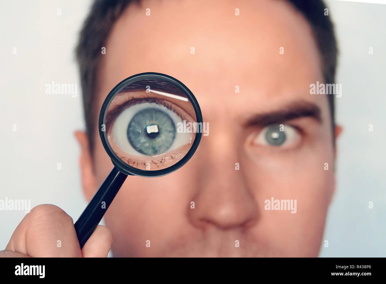 Nahaufnahme des Gesichts des Mannes mit der Lupe in der Nähe ein Auge auf weißem Hintergrund. Blick auf die Runde menschlichen Auge durch das magnifiying Glas. Neugierige Forscher. Durch die Lupe aufmerksam. Auge konzentrieren. Stockbild