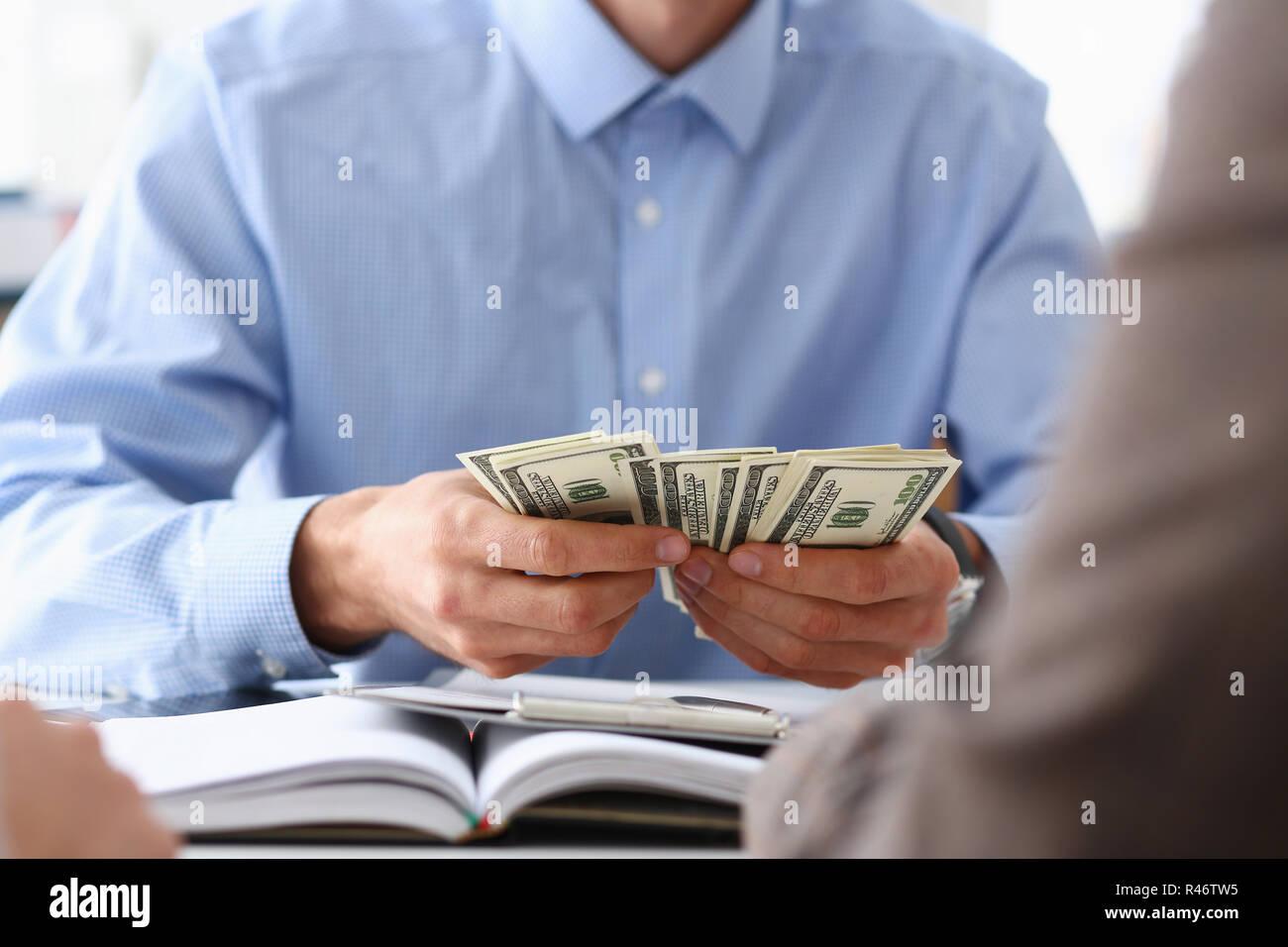 Der Unternehmer hält Bargeld Dollar im Büro Stockbild