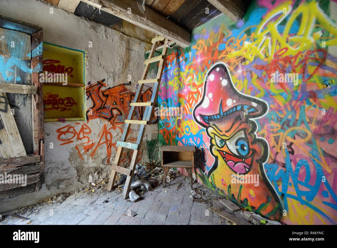 Graffiti an den Wänden, Hausgemachte wackeligen Leiter & Magic Mushroom Design in die Hocke, Interieur des verlassenen Haus Frankreich Stockbild