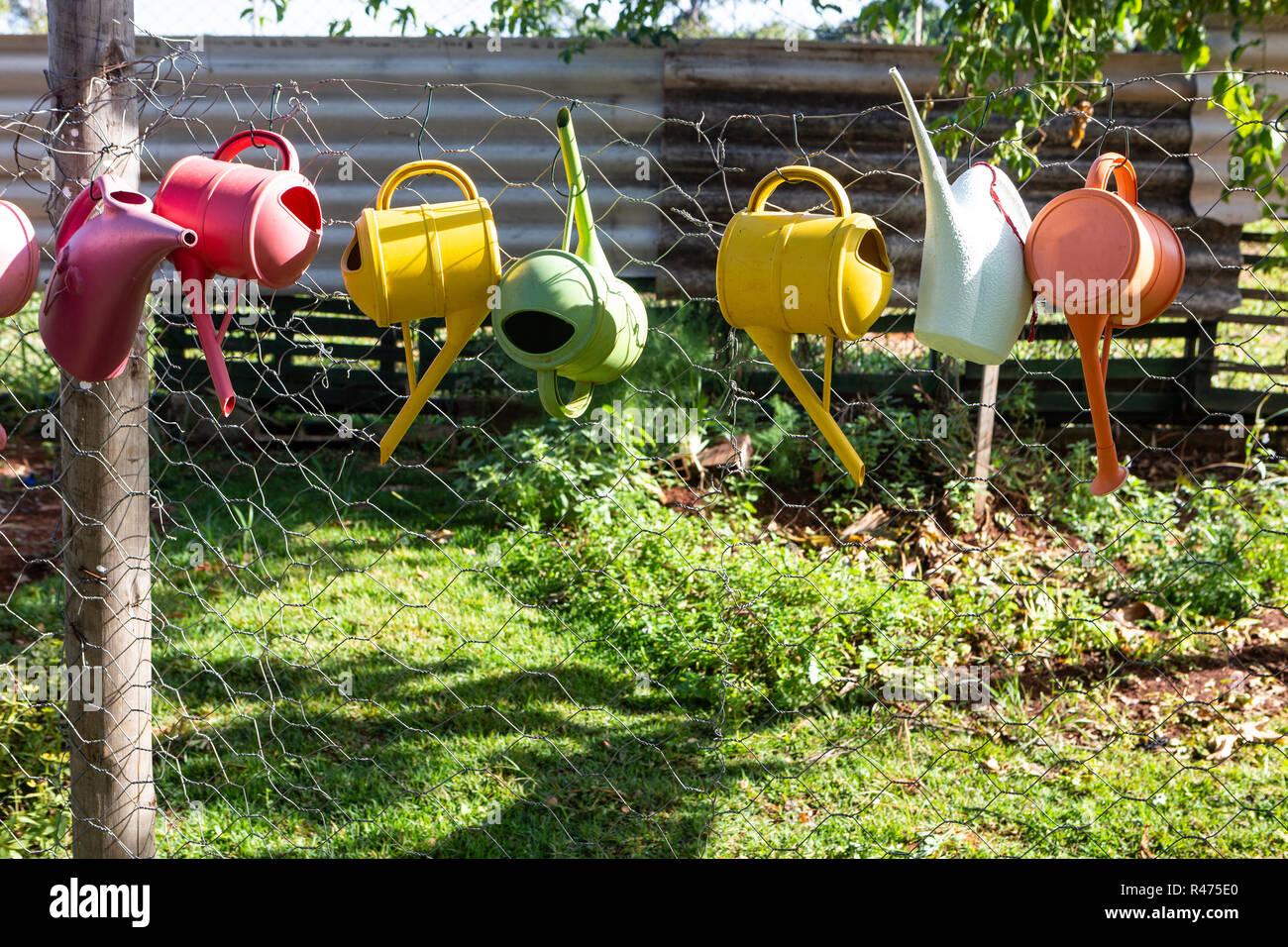 Bunte Giesskannen Am Zaun Im Garten An Einem Sonnigen Tag Stockfoto