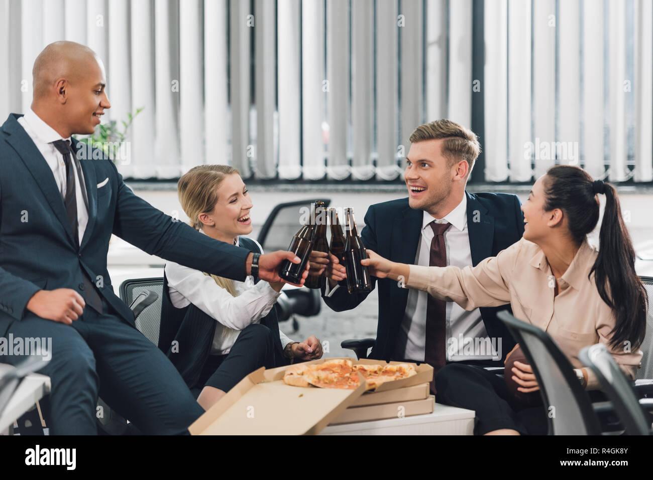 Gluckliche Junge Kollegen Bier Trinken Und Essen Pizza Im Buro
