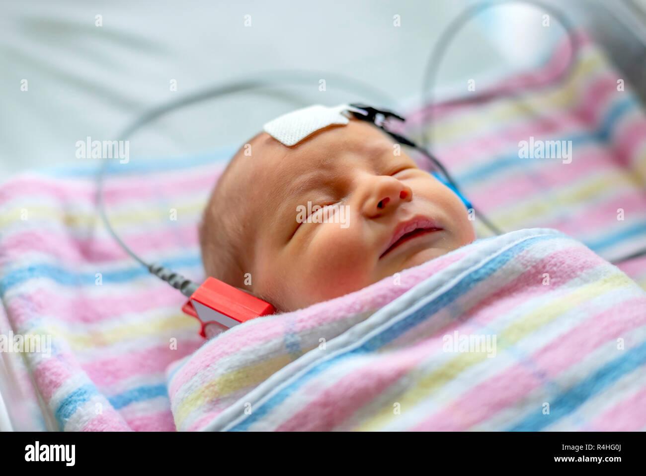 Hörfähigkeit Test eines schlafenden Neugeborenen im Krankenhaus Stockbild