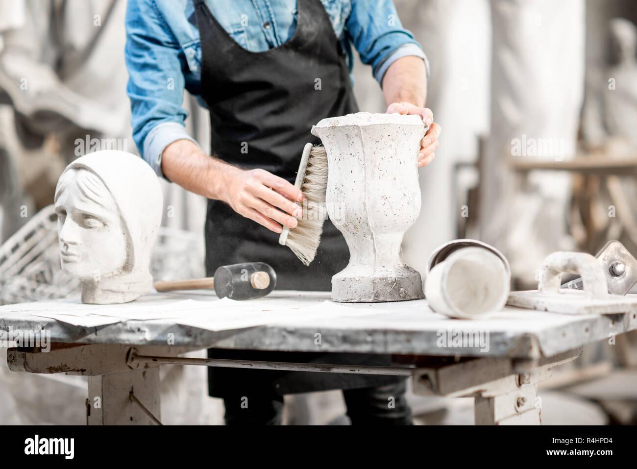 Mann bei der Arbeit mit Stein vase am Arbeitsplatz im alten Studio. Nahaufnahme mit kein Gesicht Stockfoto