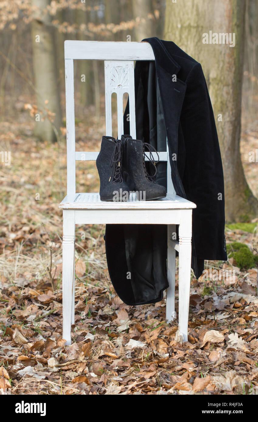 4b830b94bb36 Ein weißer Stuhl mit schwarzen Schuhe und Jacke im Wald Stockbild