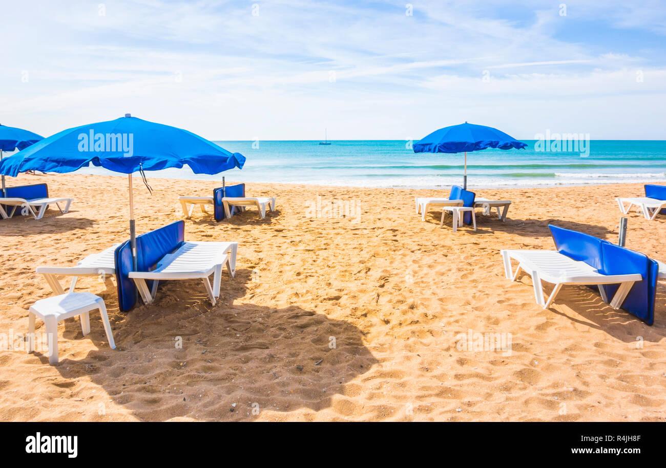 Blaue Sonnenschirme und Liegestühle am einsamen Strand, Albufeira, Algarve, Portugal Stockbild