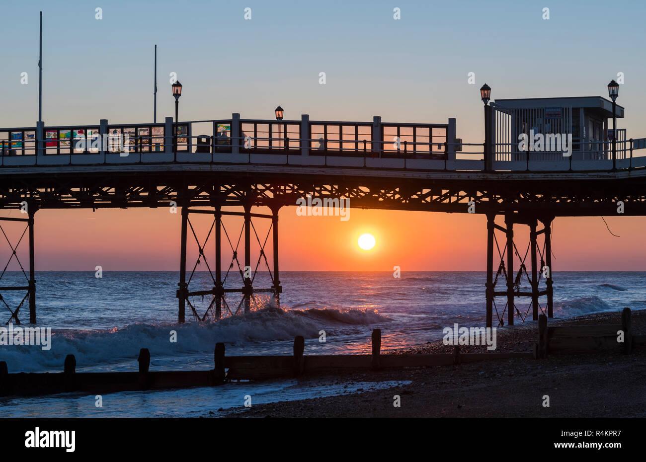 Niedrige Sonnenuntergang über dem Meer bei einem Herbst Sonnenuntergang an der Küste von Worthing Pier, West Sussex, England, UK. Stockbild