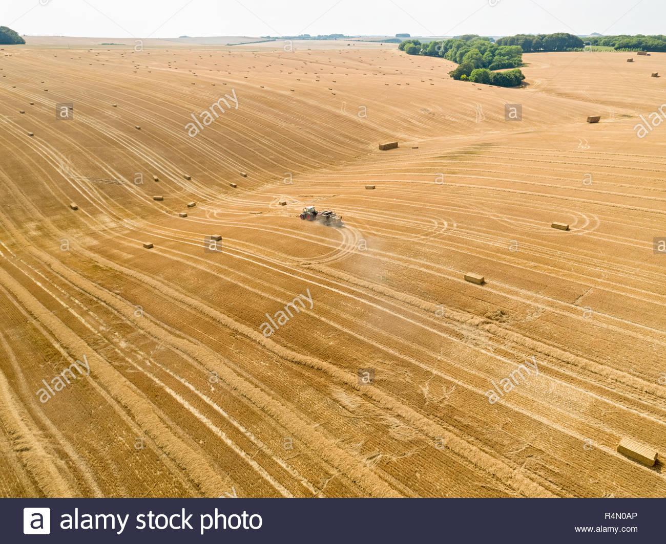 Antenne des Traktors und der Ballenpresse Strohballen in Feld nach der Weizenernte im Sommer auf der Farm Stockfoto