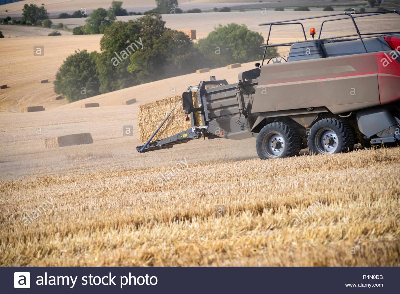 Traktor und Ballenpresse Strohballen in Feld nach dem Sommer Weizenernte auf der Farm Stockfoto