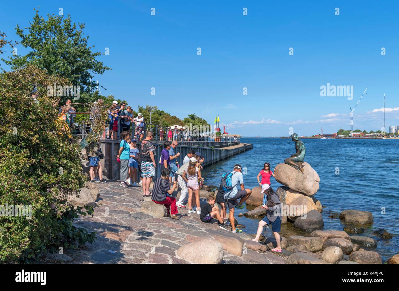 Touristen für Bilder von Die kleine Meerjungfrau (Den Lille Havfrue), Kopenhagen, Dänemark posing Stockbild