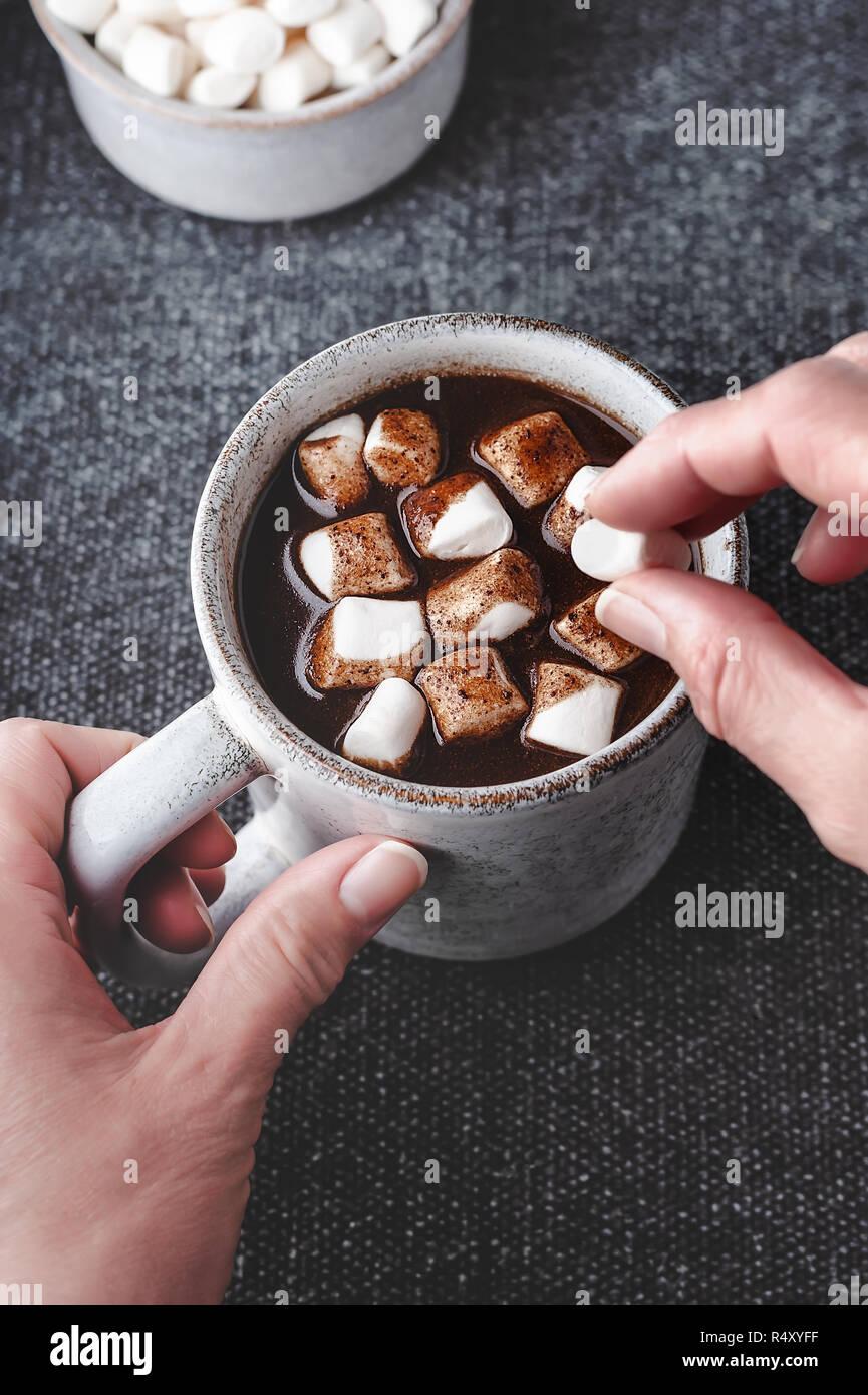 Eine Frau fügt Marshmallows zu einer Tasse heißen Johannisbrot-, eine kostenlose Alternative zu Schokolade. Stockbild