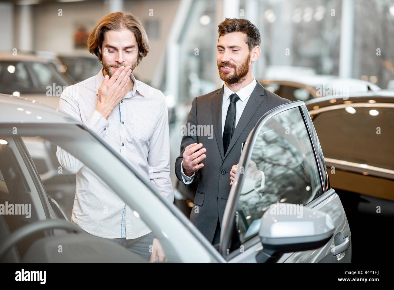 Autoverkäufer hilft einem Jungen schämen Client eine Entscheidung anzeigen intrerior eines Luxuswagens im Showroom zu machen Stockbild