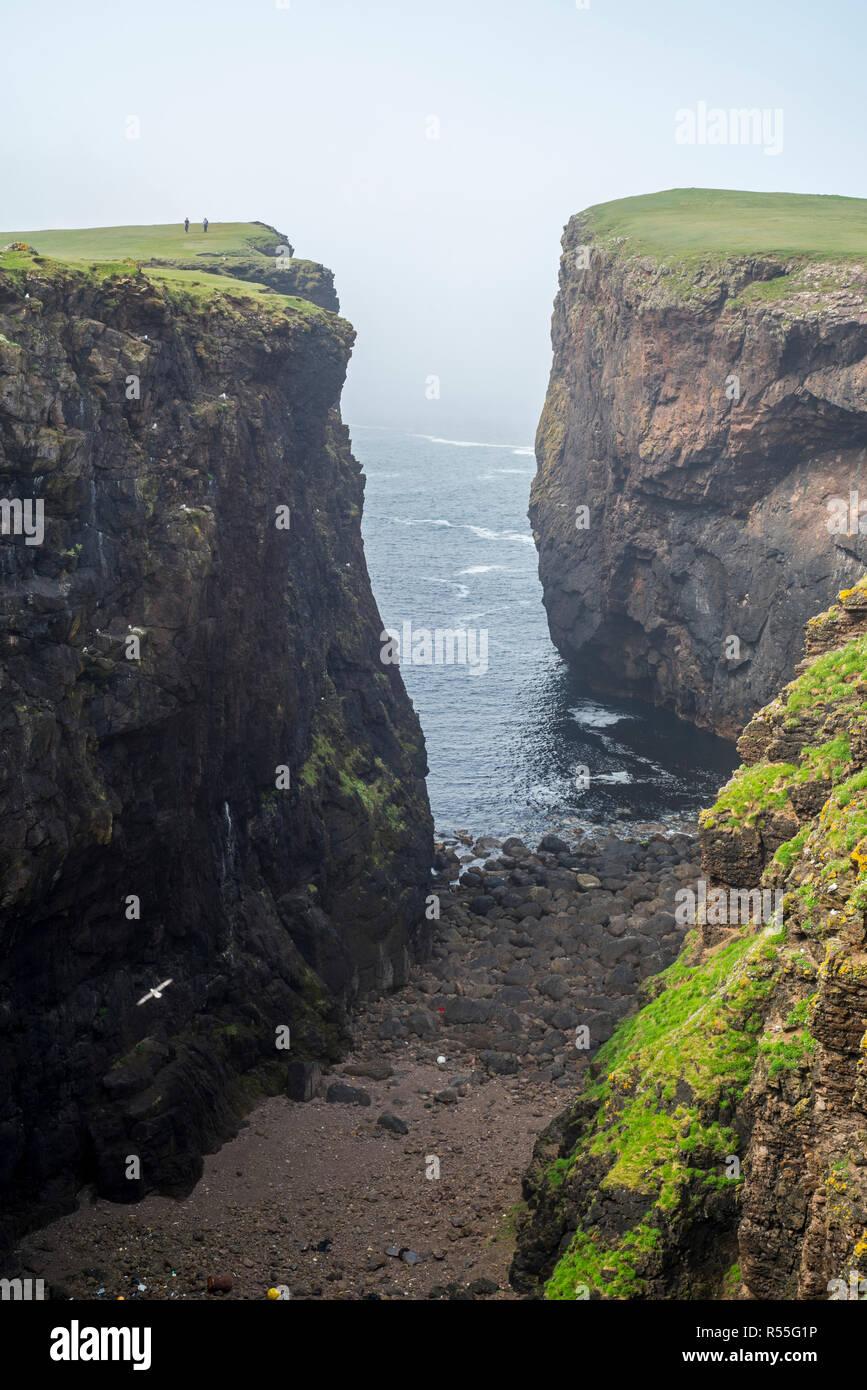 Zwei Spaziergänger Calder's Geo, tiefe Kluft in Sea Cliff bei Eshaness/Esha Ness, Halbinsel in Northmavine, Festland, Shetlandinseln, Schottland, Großbritannien Stockbild