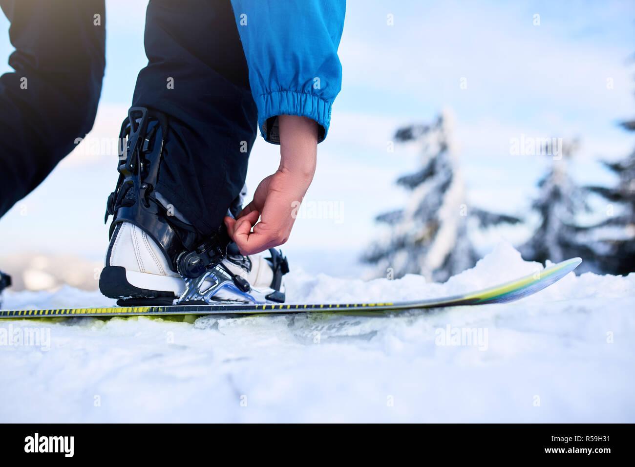 Snowboarder Bänder in seine Beine in Snowboardschuhe in modernen fast flow Bindungen mit Gurten. Reiter am Ski Resort bereitet sich für Freeride Session. Mann, der modische Outfit. Stockbild