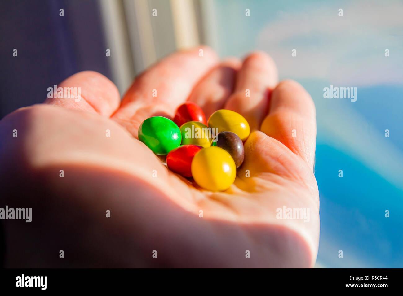 Mann hand mit bunten Schokolinsen Tasten Stockfoto