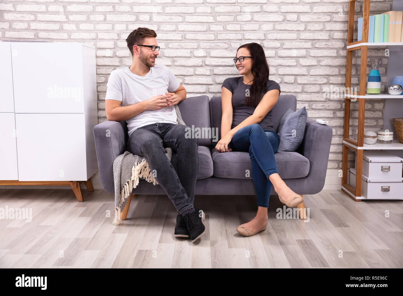 Junge Männer Und Eine Frau Sitzen Auf Einem Sofa An Einander Suchen