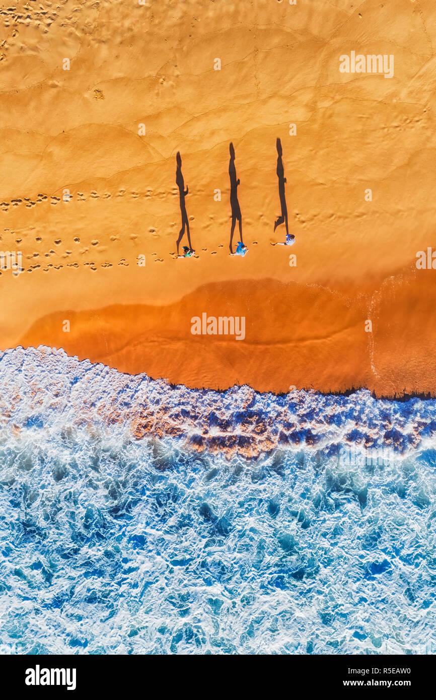 Aktiv laufen die Menschen entlang der Küste des Pazifischen Ozeans auf Sydney Northern Beaches während der Morgen excercise beleuchtet durch weiches Licht werfen lange Schatten. Stockbild