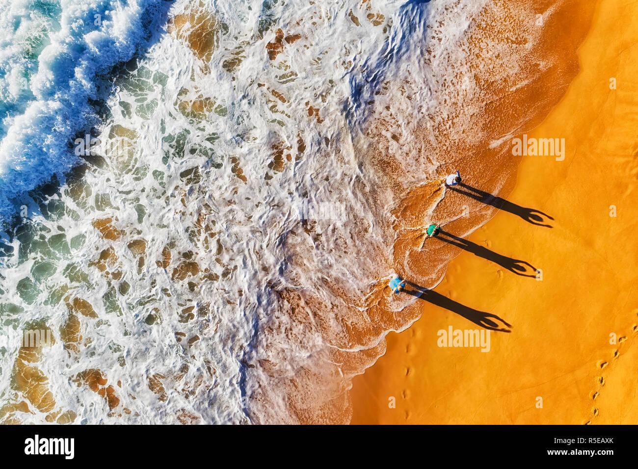 Gruppe von aktiven sportlichen gesunde Menschen ausüben, brechenden Wellen am Ufer des Pazifischen Ozeans aus breiten Sandstrand der nördlichen Strände in Australien, Sydney, Stockbild