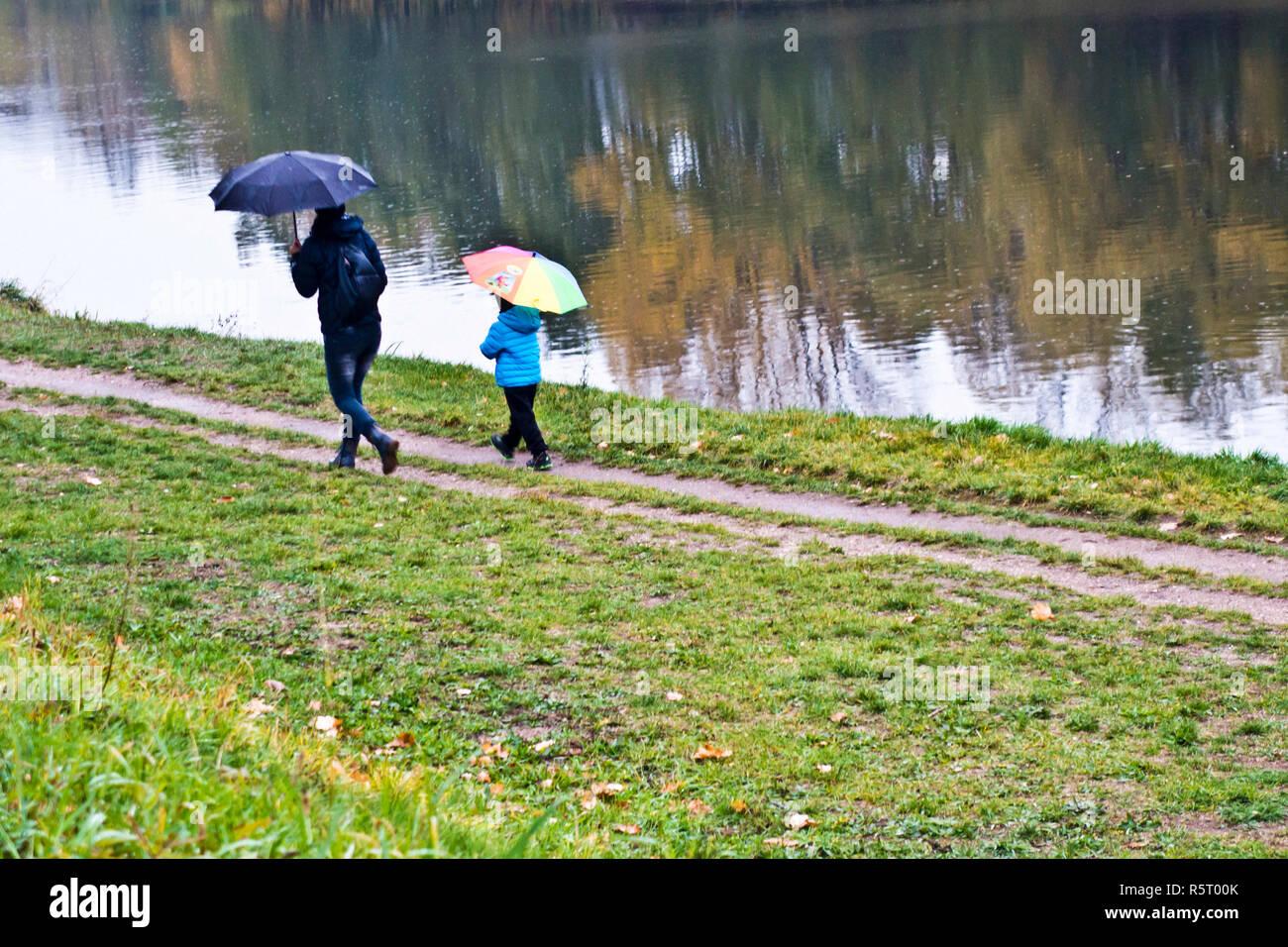 Mutter mit Kind zu Fuß entlang eines Flusses mit Sonnenschirmen an einem regnerischen Tag Stockbild