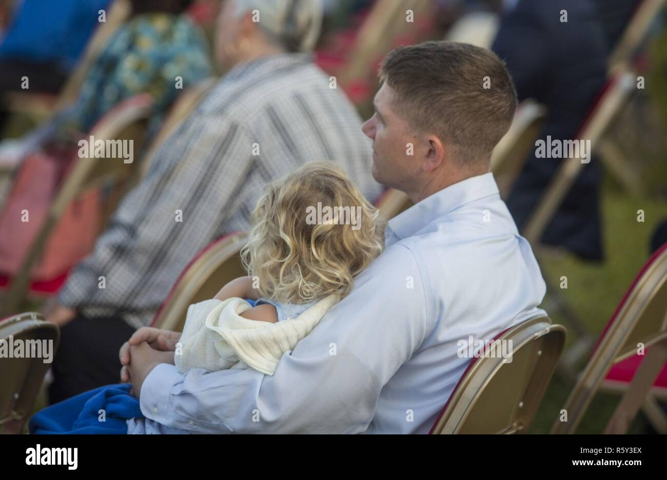 Ein Vater hält seine Tochter während der Predigt während der jährlichen Easter Sunrise Zeremonie, Camp Lejeune, N.C., 16. April 2017 hören. Jedes Jahr das Marine Corps Installationen Osten Kaplan hosts Die Easter Sunrise Zeremonie für die Marines und Seeleute, ihre Familien zu bringen und das Osterfest feiern. Stockbild