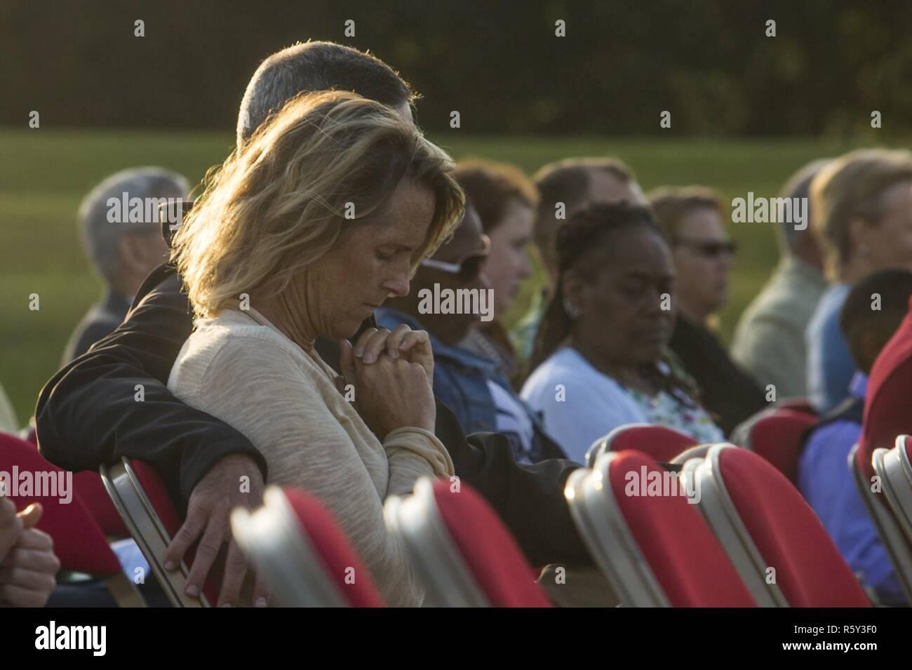 Eine Frau beugt den Kopf im Gebet während der jährlichen Easter Sunrise Zeremonie, Camp Lejeune, N.C., 16. April 2017. Jedes Jahr das Marine Corps Installationen Osten Kaplan hosts Die Easter Sunrise Zeremonie für die Marines und Seeleute, ihre Familien zu bringen und das Osterfest feiern. Stockbild