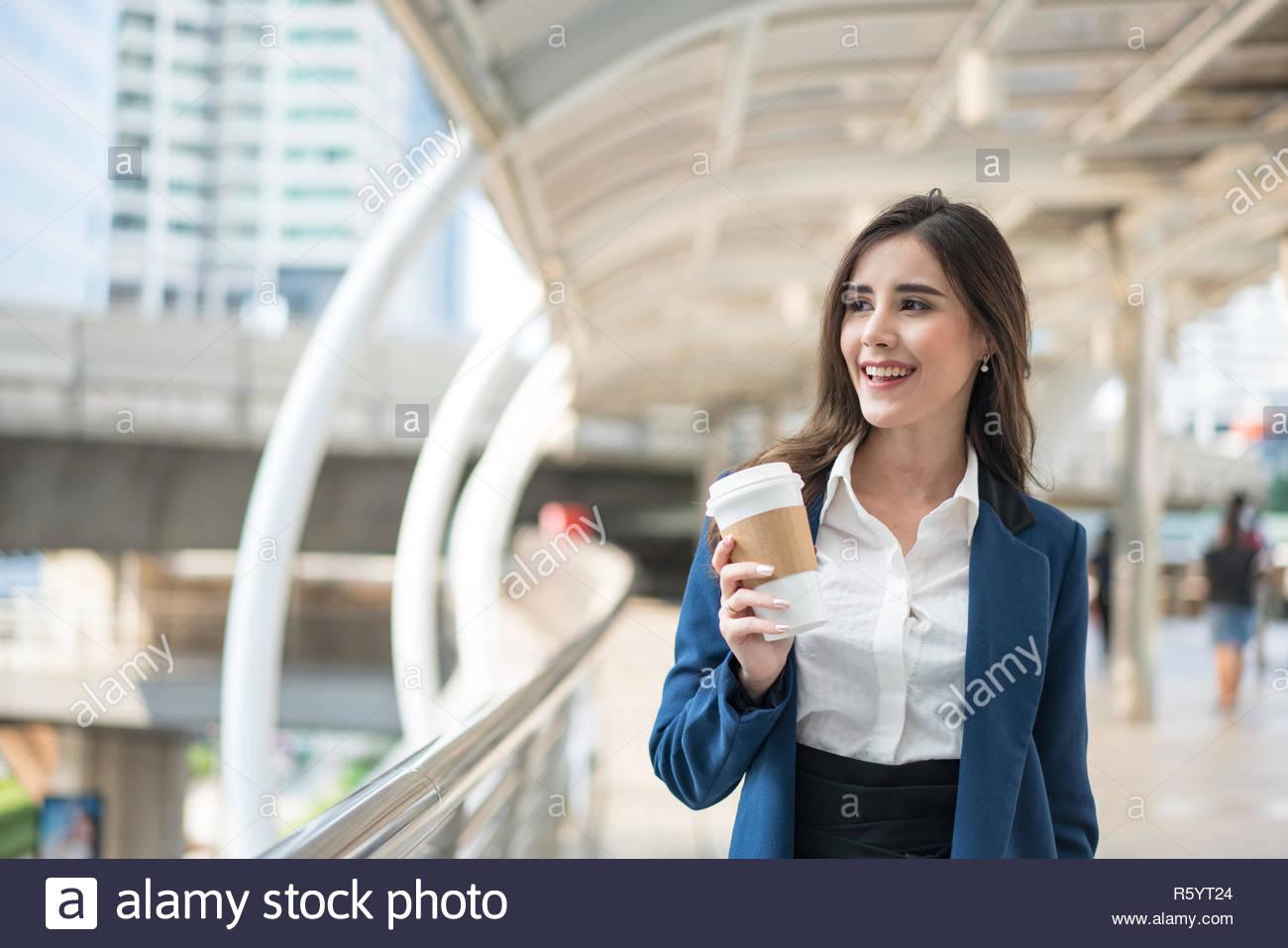 Schöne Frau geht zur Arbeit mit Kaffee zu Fuß in der Nähe des Bürogebäudes. Portrait des erfolgreichen Business Woman Holding Tasse heißen Getränk in der Hand auf Ihrem Stockbild