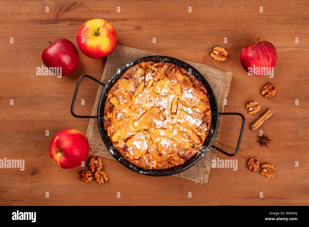 Ein apfelkuchen in der Pfanne, aus den Top Shot auf einem dunklen Holzmöbeln im Landhausstil Hintergrund mit Äpfeln, Nüssen, Zimt, Anis, und kopieren Sie Platz Stockfoto