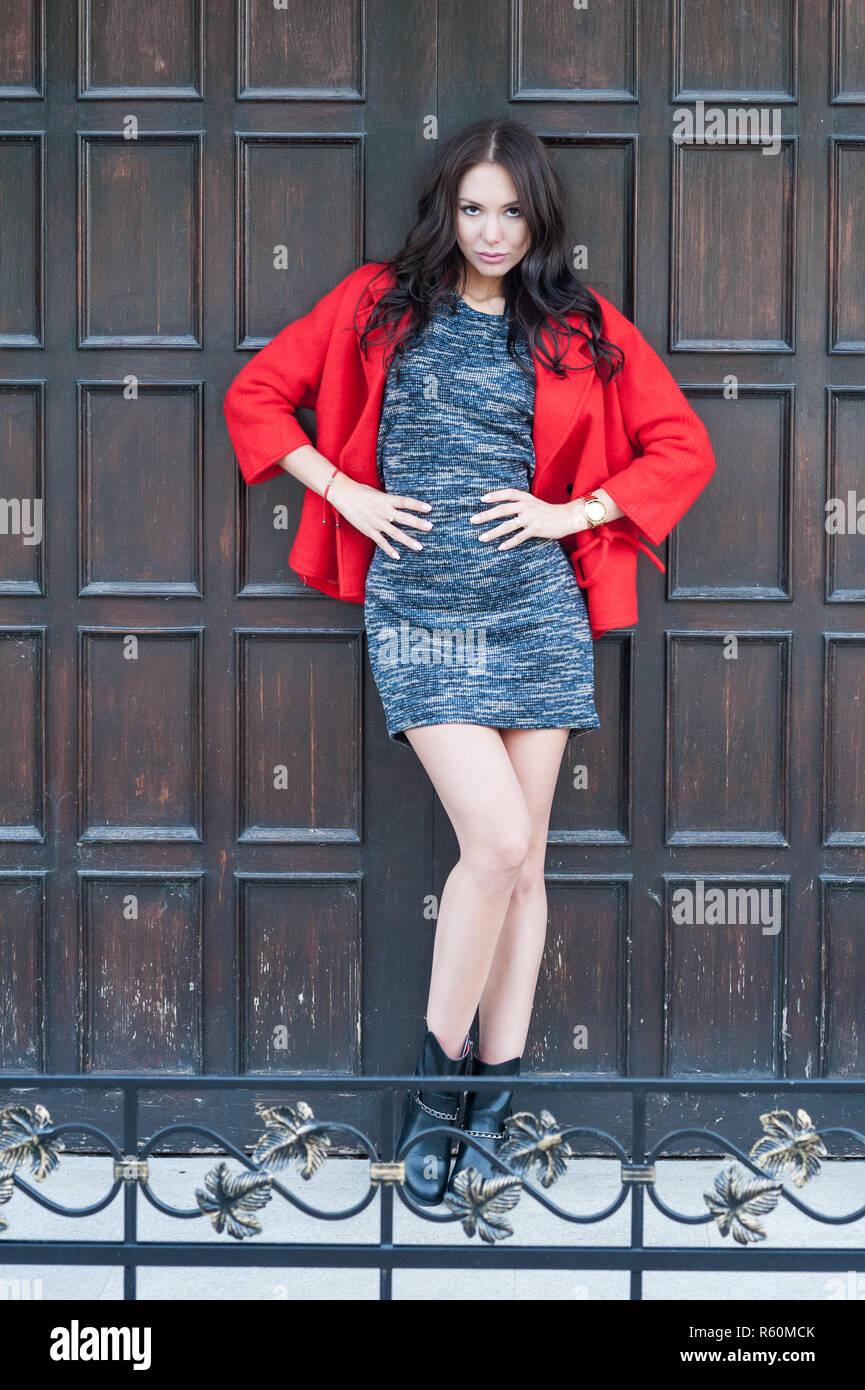 72ef647e8b2e47 Junge schöne stilvolle Frau in einem roten Mantel bekleidet
