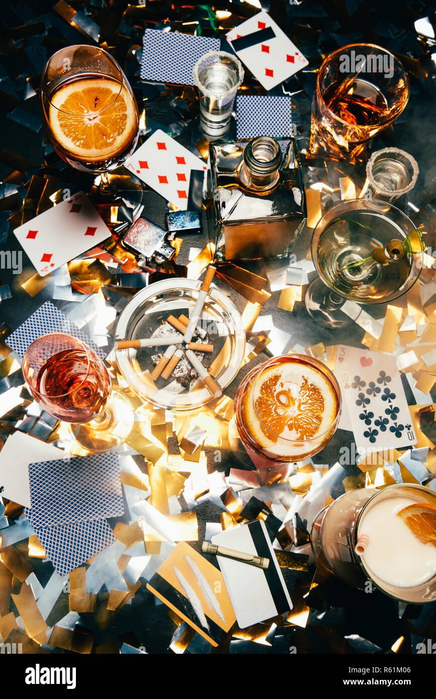 Blick von oben auf die Zigaretten, alkoholische Cocktails, Karten spielen, gerollte Banknoten, Kreditkarten und Kokain auf Tabelle von golden Konfetti bedeckt Stockfoto